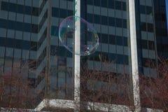 Såpbubbla som flyger över stadsbakgrundsbyggnad Royaltyfri Bild