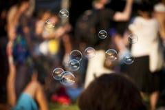 Såpbubblor med folkmassan i bakgrund på sommarmusikfestivalen Royaltyfri Bild