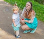 Såpbubblor på en tillåten gå modern och barnet Fotografering för Bildbyråer