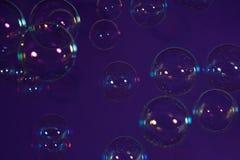 Såpbubblor på en violett bakgrund arkivfoto