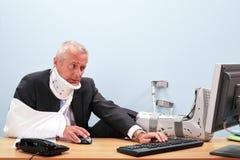 Sårad affärsman som fungerar på hans skrivbord royaltyfri fotografi