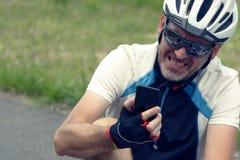 Sårad cyklist som rymmer hans smartphone som kallar räddningsmanskapet Royaltyfri Foto
