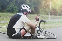 Sårad cyklist som rymmer hans smartphone som kallar räddningsmanskapet Royaltyfria Bilder