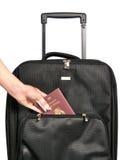 Sårad hand som sätter passet i resväska under en semester Royaltyfri Foto