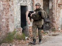 Sårad kvinna och soldat i likformig för polsk armé under Histori Royaltyfria Bilder