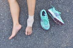 Sårad löpare som sitter på vägen royaltyfri foto