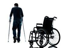 Sårad man med kryckor som går i väg från rullstolsilhou Arkivfoto