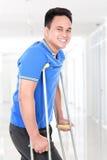 Sårad ung man som går med hjälpen av kryckor Arkivfoton