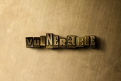 SÅRBART - närbild av det typsatta ordet för grungy tappning på metallbakgrunden Royaltyfri Foto