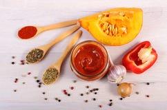 Sås av pumpa i den glass kruset, kryddor och ingredienser på trätabellen Arkivbilder