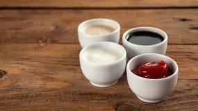 Såser ketchup, senap, majonnäs, gräddfil, soya i lera bowlar på träbakgrund Arkivbilder