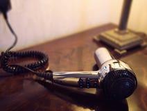 Sèche-cheveux argenté sur une coiffeuse en bois photo libre de droits