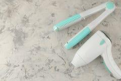Sèche-cheveux et fer de bordage accessoires pour des soins capillaires sur une vue supérieure de fond de ciment avec l'espace pou photo stock