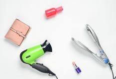 Sèche-cheveux, fer de cheveux, rouge à lèvres, bouteille de parfum, bourse d'isolement sur le fond blanc Photo libre de droits
