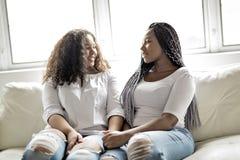 Séance afro-américaine d'amis affectueux sur le sofa photos stock