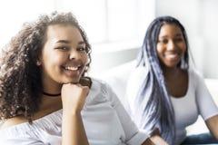 Séance afro-américaine d'amis affectueux sur le sofa Photo stock