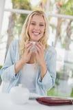 Séance assez blonde à la table ayant le café souriant à l'appareil-photo Photographie stock libre de droits