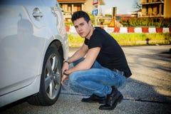 Séance belle d'homme sans compter que la roue de la voiture Photo stock