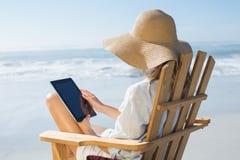 Séance blonde de sourire sur la chaise de plate-forme en bois par la mer utilisant le comprimé photos stock