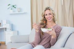 Séance blonde de sourire sur le divan mangeant de la salade images stock
