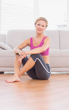 Séance blonde sportive sur le plancher souriant à l'appareil-photo photographie stock libre de droits