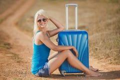 Séance blonde sur des valises sur le côté de la route Photo stock