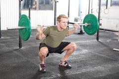 Séance d'entraînement accroupie au centre de gymnase de forme physique Photo stock