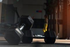 Séance d'entraînement avec des haltères Fond brouillé de gymnase Photographie stock libre de droits