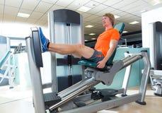 Séance d'entraînement blonde d'homme de machine de presse de jambe posée par gymnase photographie stock libre de droits