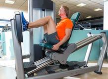 Séance d'entraînement blonde d'homme de machine de presse de jambe posée par gymnase image libre de droits