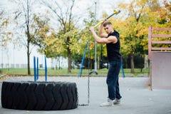 Séance d'entraînement d'homme de sport de forme physique extérieure avec le pneu de marteau et de tracteur photographie stock libre de droits