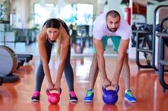 Séance d'entraînement d'homme et de femme d'exercice d'oscillation de Kettlebells au gymnase Photographie stock libre de droits