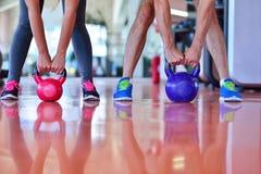 Séance d'entraînement d'homme et de femme d'exercice d'oscillation de Kettlebells au gymnase Image libre de droits