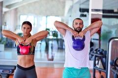 Séance d'entraînement d'homme et de femme d'exercice d'oscillation de Kettlebells au gymnase Image stock