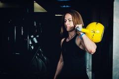 Séance d'entraînement de cloche de bouilloire de femme dans le gymnase Femme musculaire tenant la cloche de bouilloire Images stock
