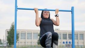 Séance d'entraînement de femme de forme physique faisant des exercices sur une barre horizontale dehors images stock