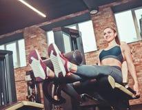 Séance d'entraînement d'exercice d'extension de jambe smilling la femme sportive photographie stock libre de droits