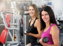 Séance d'entraînement sportive de deux femmes avec l'haltère dans le gymnase photographie stock libre de droits