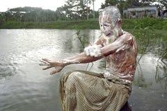 Séance d'homme très vieil pour se laver au coucher du soleil Image libre de droits