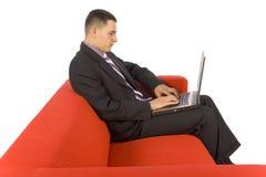 séance d'ordinateur portatif de divan d'homme d'affaires Photo libre de droits