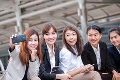 Séance de femme d'affaires et téléphone d'utilisation pour prendre la photo comme WI de selfie Photos libres de droits