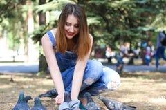 Séance de femme et graines de pigeons d'alimentations Photographie stock