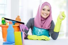 Séance de jeune femme tout en nettoyant une table avec le supplie de nettoyage photographie stock