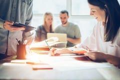 Séance de réflexion joyeuse d'équipe Nouvelle recherche de plan marketing Écritures à la table, à l'ordinateur portable et au tél photographie stock libre de droits