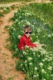 Séance de repos de garçon sur l'herbe pendant une promenade de pays photographie stock libre de droits