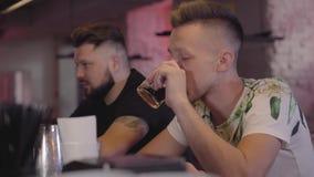 Séance de sourire de deux hommes adultes au rhum potable de compteur de barre Amis masculins décontractés refroidissant l'alcool  banque de vidéos