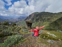 Séance de touristes de jeune femme sur le bord du ` s de falaise Image libre de droits