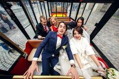 Séance drôle de sembler de jeunes mariés avec des amis dans un tra de touristes Image stock