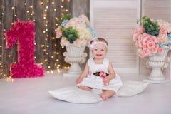 Séance an du bébé 1-2 mignon sur le plancher avec les ballons roses dans la chambre au-dessus du blanc D'isolement Fête d'anniver photos stock
