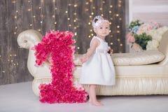Séance an du bébé 1-2 mignon sur le plancher avec les ballons roses dans la chambre au-dessus du blanc D'isolement Fête d'anniver photo stock